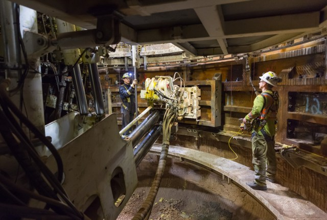 Workers in the production shaft at BHP Billiton's Jansen Project, control the installation of steel tubbing by the Herrenknecht Shaft Boring Roadheader.