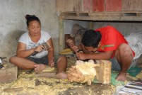 Wood carvers working in their shop