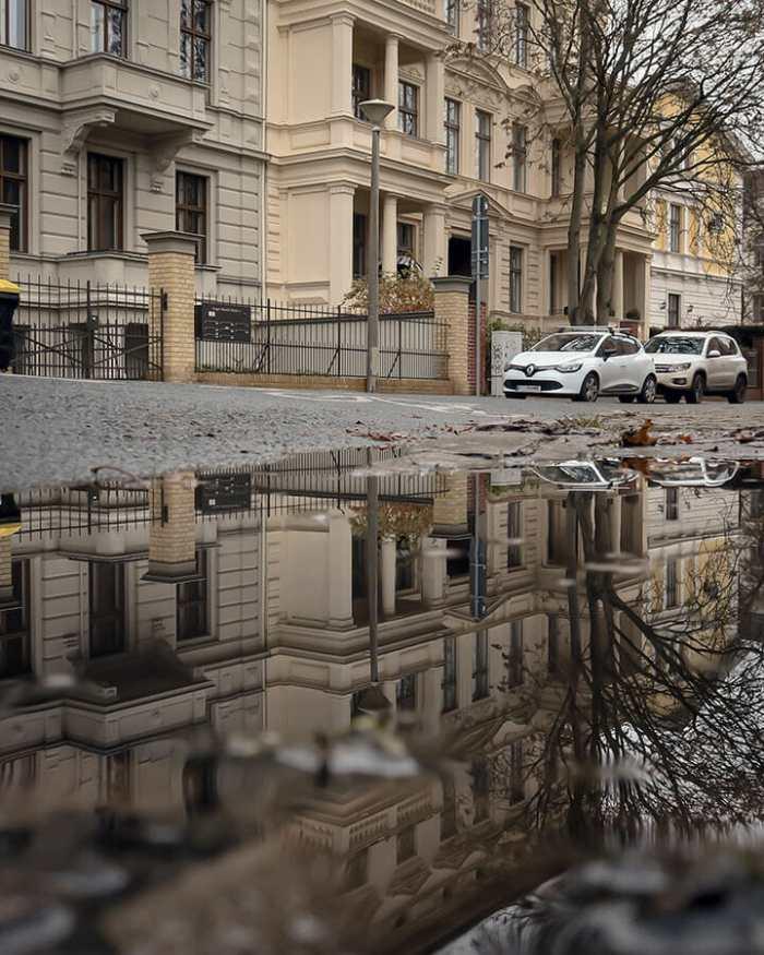 Häuser spiegeln sich in der Pfütze.