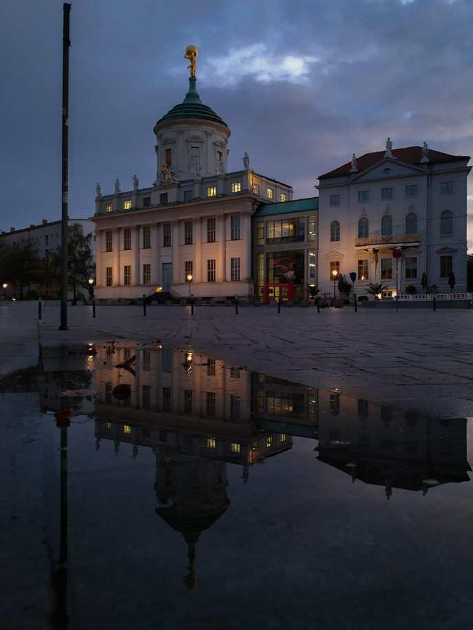 Das Alte Rathaus spiegelt sich im Morgengrauen in einer Pfütze
