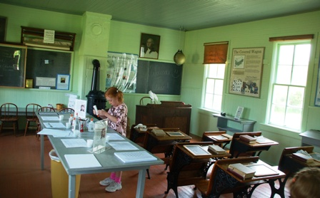 This was a replica of the school Laura and her sisters attended. Inside was a hands-on discovery area. In this photo, Chic is writing her name in braille by gluing split peas to paper.