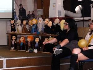 Na fotografii je polička položená na podiu a na ní šití maňásci postav z Harryho Pottera. Vpravo na pódiu sedí jedna z účastnic festivalu.