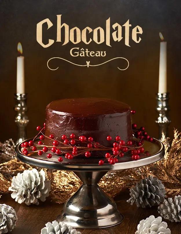 Čokoládový dort na vysokém kulatém a stříbrném stojanu. Kolem dortu se nacházejí ozdoby v podobě červených lesklých kuliček. V pozadí jsou dvě vysoké bílé svíčky a k dozdobení na bálo obarvené šišky a zlaté listy.