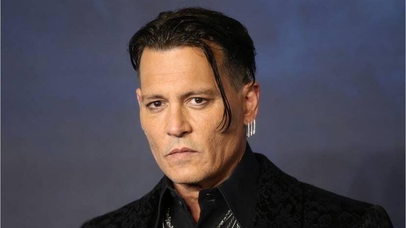 Zachmuřený obličej oholeného Johnyho Deppa. Na levém uchu má tři dlouhé stříbrné náušnice.