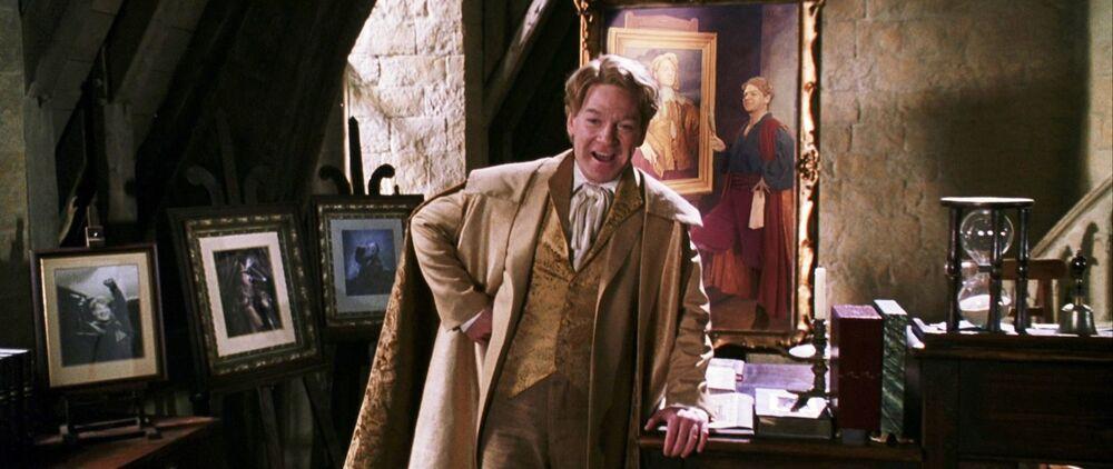 """Profesor Lockhart v učebně obrany proti černé magii. Okolo něj je spousta jeho obrazů a portrétů. Opírá se o stůl levou rukou, pravou ruku má zapřenou v bok a snaží se vytvářet dojem """"velkoleposti"""", což se mu na této fotce nedaří, protože má přihlouple pootevřená ústa."""