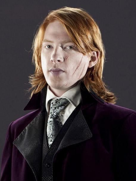 Fotografie Billa Weasleyho, který je oblečen do tmavofialového hábitu s černým límečkem v podobě hadí kůže. Má černo-bílou ornamentální kravatu a bílou košili.