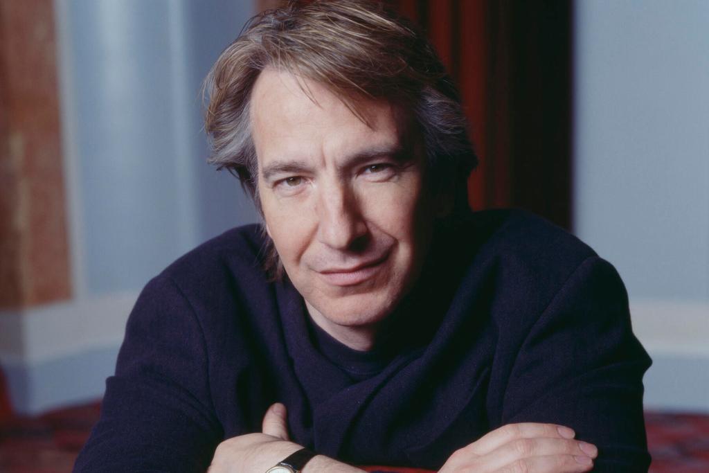Fotografie obličeje herce, který se dívá do objektivu. Má světle hnědé a šedé, delší a upravené vlasy a nasazený mírný úsměv. Je vidět část jeho založených rukou na hrudi. Má na sobě černý svršek s dlouhými rukávy.
