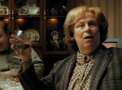 Fotografie z filmu Vězeň z Azkabanu. Teta Marge sedí u stolu čelem k divákovi, ale kouká kamsi za něj. Má pootevřená ústa, jako by něco říkala. V pravé zdvižené ruce má sklenku s alkoholem.