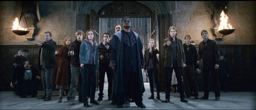 Fotografie z filmu Harry Potter a Relikvie smrti, 2. část. Před vchodem do Velké síně, osvětlené pochodněmi z obou stran je velká skupina kouzelníků. Uprostřed je Kingsley Pastorek, zleva od něj Neville, Hermiona, Ron, Molly, Arthur, Kratiknot a Prýtová. Zprava od Pastorka stojí Fleur, Bill, Fred a George. Všichni drží své hůlky připraveni s nimi bojovat.