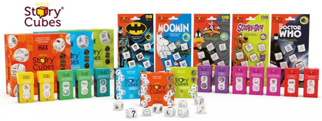 Na širokoúhlém obrázku je ve dvou řadách vedle sebe celkem 23 sad s kostkami v různých barvách. Vlevo nahoře je je logo Rory's Story Cubes.