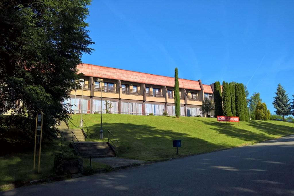Na fotografii je uprostřed podlouhlá budova, jejíž přízemí je převážně zasklené. V prvním poschodí jsou vedle sebe balkóny a na všem vybledlá červená střecha. Napravo i nalevo od hotelu, který stojí na vyvýšeném travnatém kopečku, jsou stromy. V pravém dolním rohu je silnice.