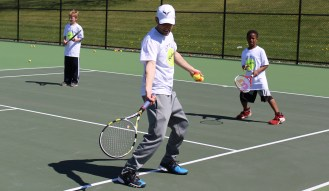 Greater Pottstown Tennis & Learning instructor Chris Herdelin teaches children some basics of the sport during the combined PEAK Pottstown Celebrates Young Children and YMCA Healthy Kids Day event Saturday.