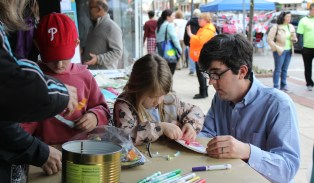 Sam Gilbert, right, works on an arts and craft project with his children Violet, 4, and Peter,7, during the first outdoor farmers market in Pottstown in the 200 block of High Street.
