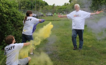 "Ron Miller, the father of the late Ian Miller, walks through yellow and purple powder during a color run fundraiser at West-Mont Christian Academy Saturday. The event raised money for a nonprofit shoe organization called ""In Ian's Boots,"" which was created in the memory of Miller's son."