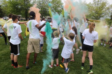"People who participated in a color run use the last of the powder on one another after the race at West-Mont Christian Academy Saturday. The event raised money for the nonprofit organization ""In Ian's Boots"" which provides shoes to those in need."