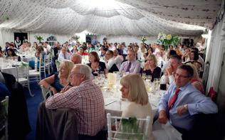 Wedding party listening to speeches in reception marquee