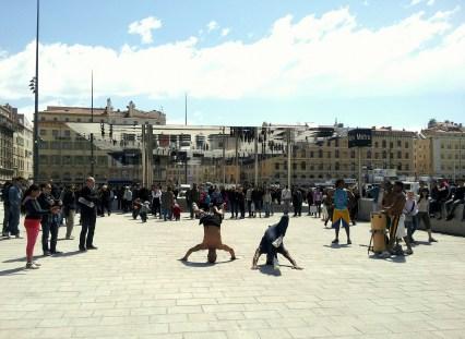 """Faire plus de place aux piétons permet de nouvelles appropriations de l'espace public, notamment par la musique et la danse. L'opération de semi-piétonnisation du Vieux-Port de Marseille a aussi permis d'insérer une """"ombrière"""" en miroir avec la rue. Meilleur Espace Public Européen de l'année 2014 (avec Braided Valley à Elche) Crédit photo: Julia Z. http://bit.ly/1qli3Mx"""