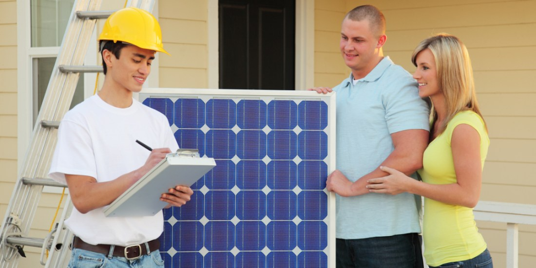 Couple standing next to solar panel and construction worker holding a clipboard.