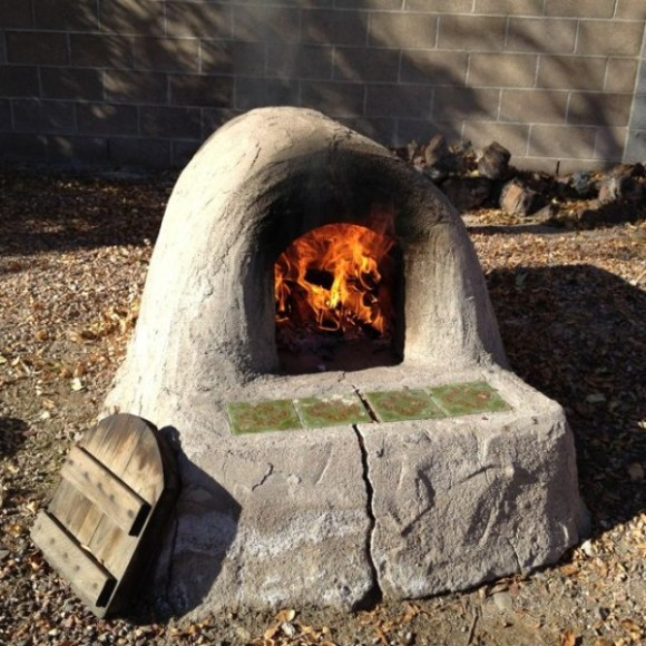 Readying the outdoor adobe oven for bread.