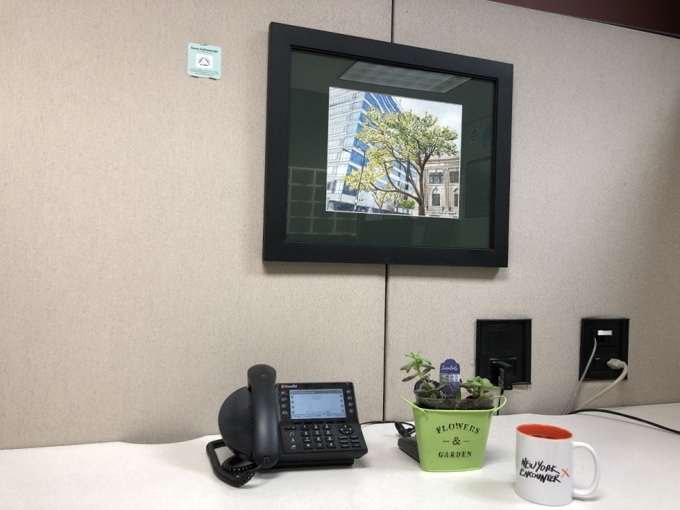 Cubicle with painting showing a sleek, modern, blue building to the left of a classical tan building with a mature tree with new buds in between. I work in the modern building, but I LOVE the classical building with its trees. Also, my wife's business card, a phone which hardly ever rings, succulents, and a New York Encounter mug.