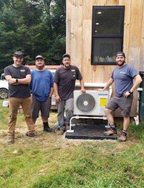 4 men standing outside next to mini-split