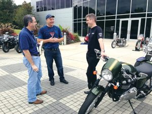 In a meeting of CEOs, a reporter visits with Greg Heichelbech (Triumph North America), middle, and Nick Bloor (Triumph Motorcycles Ltd) during the dealer meeting at Barber Motorsports Park in Birmingham, Ala.