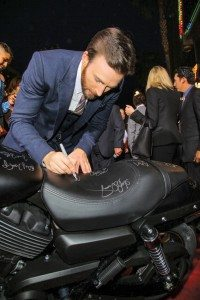 "Marvel's ""Captain America: The Winter Soldier"" star Chris Evans signs a new Harley-Davidson Street 750 at the premiere in Hollywood, Calif. Following the premiere, Harley-Davidson will donate the bike to Concord Youth Theatre."