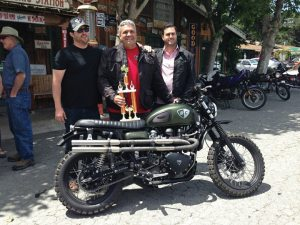 "Bryan H. Carroll (center) holding the Quail Ride ""Most Unique"" trophy with the founders of British Customs, Jason Panther and James Panther."