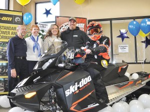 Emil And Sheila Orcholski, Make-A-Wish Wisconsin volunteers; Debbie and Kevin Wilcox, Collin's parents; and Collin (seated) on his new 2015 Ski-Doo Renegade 600 Sports snowmobile at Cedar Creek Motorsports in Cedarburg, Wis.