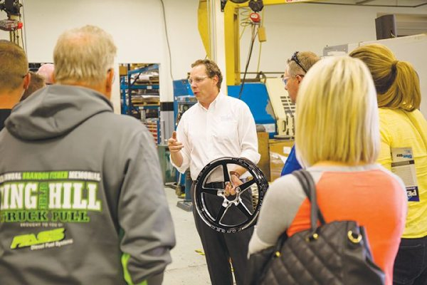 Chris Bovis, vice president of marketing at WELD, discusses the WELD Alumastar wheel at the ribbon cutting open house in Kansas City.