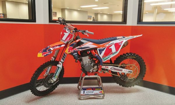 Ryan Dungey's AMA Supercross bike sits in KTM North America headquarters, as employees in the room behind it work to improve it for the next racing season.