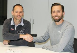 Robert Jonas (left), vice president of Husqvarna Motorsport, and Ghislain Huot, CEO of SHOT Race Gear, celebrate their companies' new partnership.