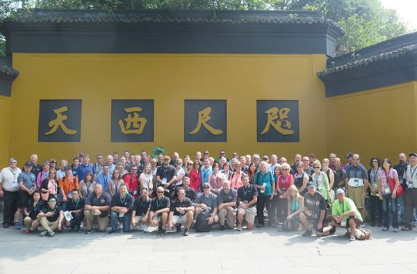 "First stop on the tour of Hangzhou, CFMOTO's hometown, was the Lingyin Temple, a Buddhist temple that is known for its grottos and rock carvings. The writing on the yellow wall translates roughly into ""Western Paradise Within Reach."""
