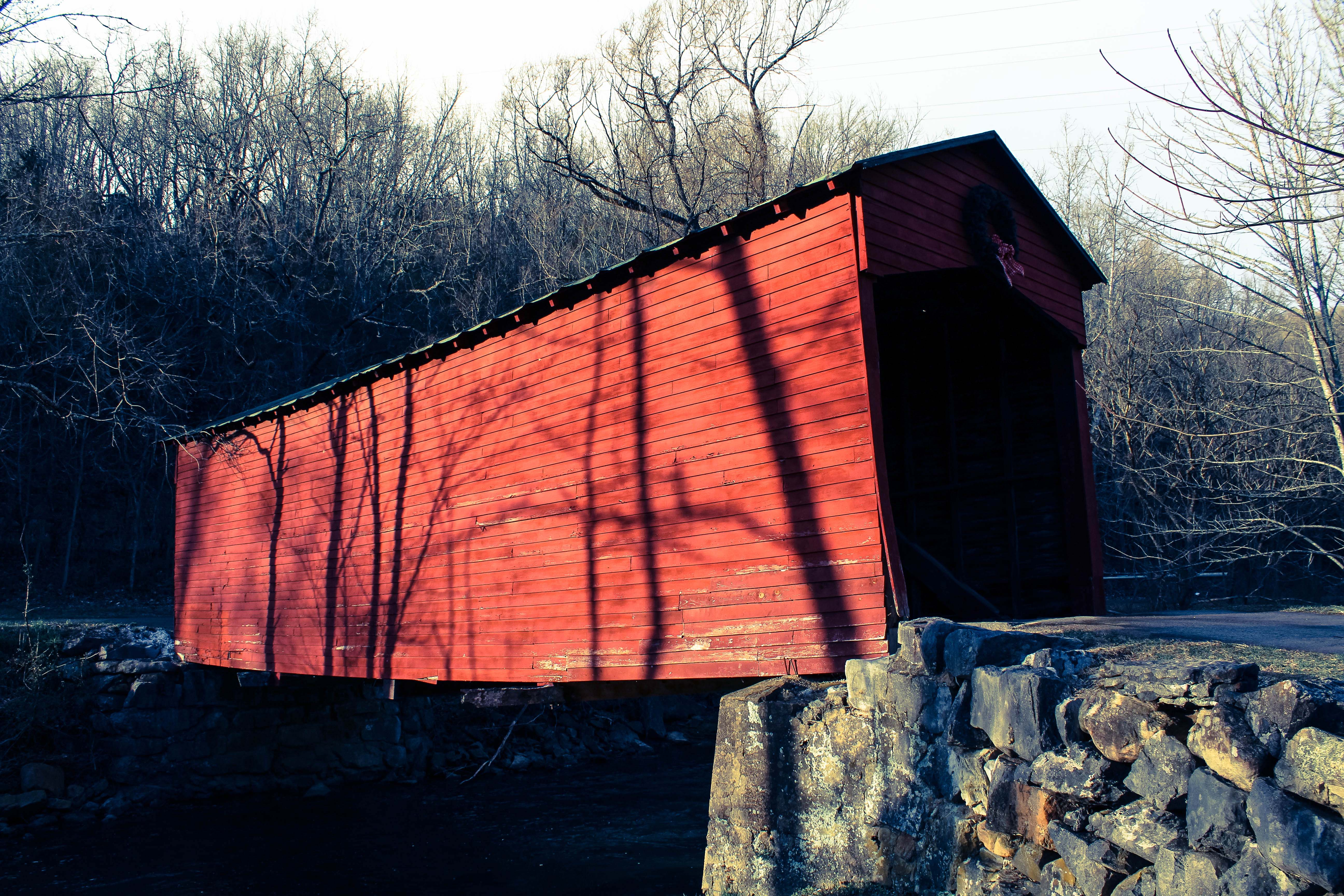 Covered bridge with shadows of trees.