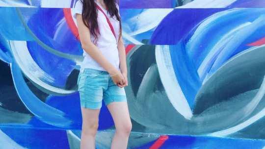 Длинноволосая  шатенка в синих джинсовых шортах