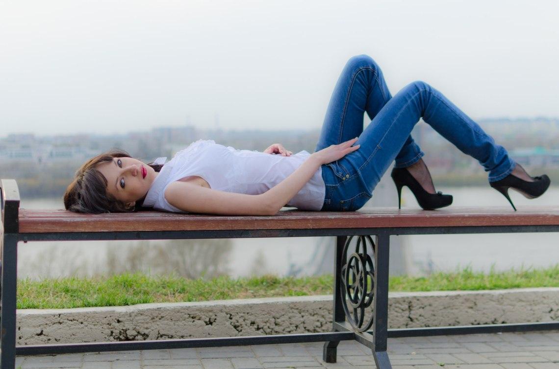 Красотка-шатенка на скамейке на фоне озера