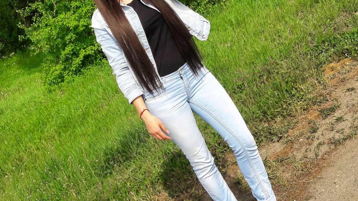 Длинноволосая девчонка брюнетка в джинсах