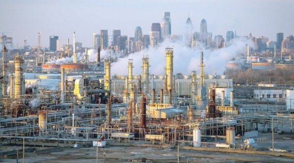 Philadelphia skyline on a clear day. White steam billows up from the refinery below, entire oil refinery comes into view.