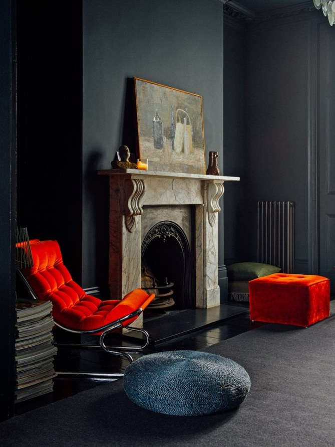 A beautiful old fireplace in a Victorian living room is flanked by a vivid, bright blood orange modern armchair, as well as an ottoman in the same color on the otherside. The armchair has silver curved legs. The walls are black.