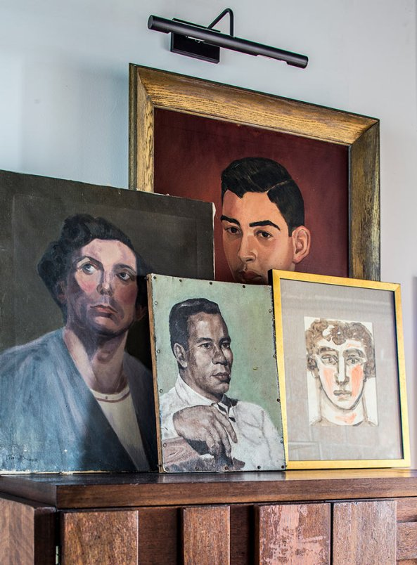 Four vintage portraits are layered on top of one another on a console table. There's a gallery light above.