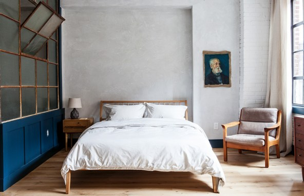 In a hotel bedroom, a vintage portrait with a blue background plays off of the blue paint color of the wainscotting.