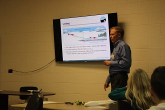 John explains the landing phase of flight and showed students how to calculate feet per minute and feet per mile.