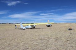An SUV towing the glider to the end of the runway. A member of the club walks alongside the wing to balance the glider and keep the wing parallel to the ground. As the launch begins and the glider accelerates, the launch crewmember/wing runner runs alongside the glider, holding the wing level until the glider has enough speed to balance on its own.