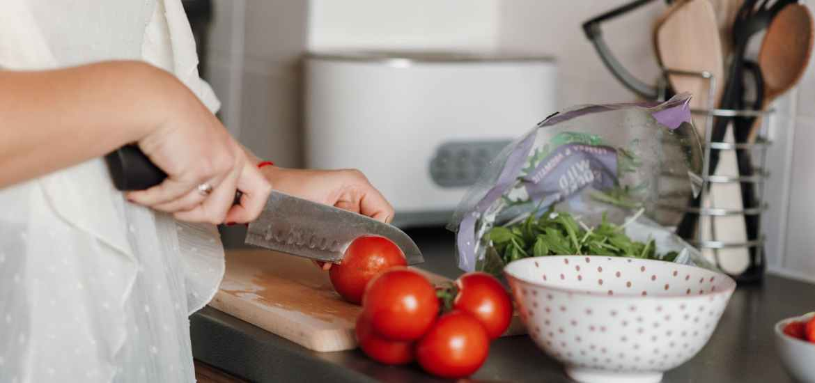 crop woman cutting tomatoes in kitchen