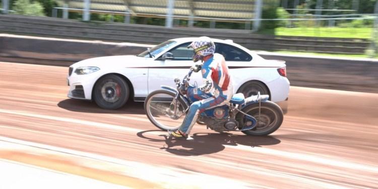 M23i drifts against a speedway bike