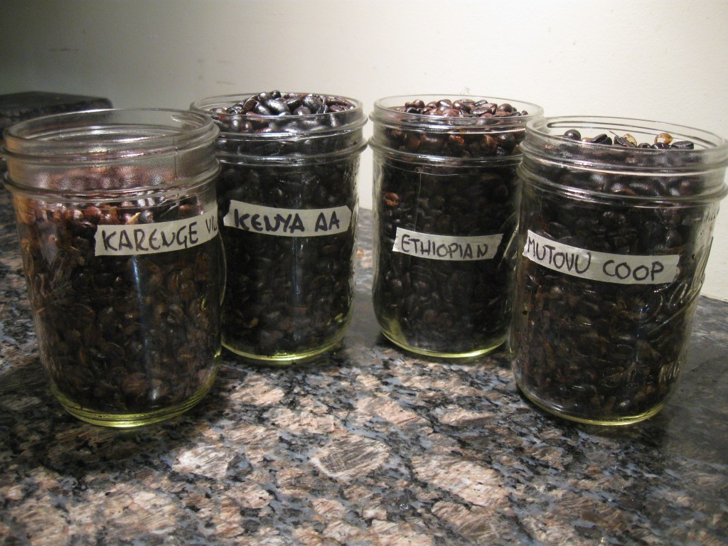 Four batches of home roasted coffee beans, each with a different country or origin.