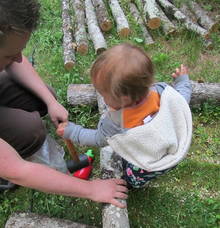 Inoculating maple logs with shiitake mushroom plugs with our 14-month-old child.