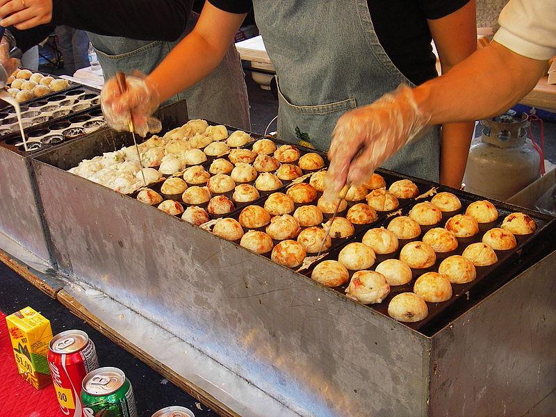 A street vendor preparing Takoyaki in a commercial pan.