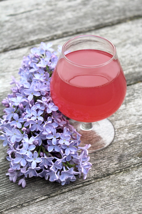 glass of lilac wine on a table with lilac flowers