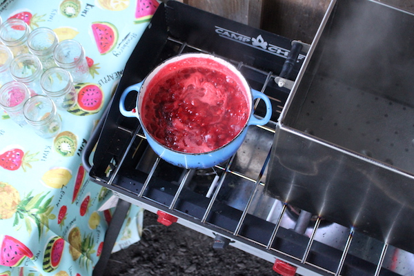 Cooking strawberry jam in an outdoor canning kitchen in a dutch oven on a 3 burner stove